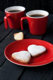 Tasse rouge et coeurs de biscuits sur une surface noire pour la saint-valentin