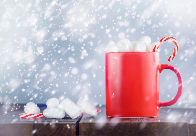 Une tasse rouge avec du chocolat chaud sur une table en bois à l'extérieur
