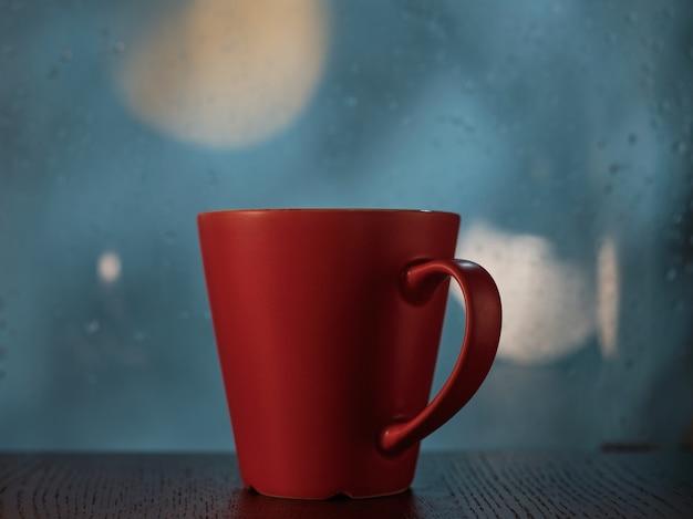 Tasse rouge sur le fond d'une fenêtre avec des gouttes de pluie