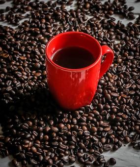 Tasse rouge avec des grains de café