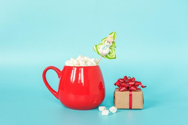 Tasse rouge de guimauve avec arbre de noël sucette verte et coffret cadeau sur fond bleu.
