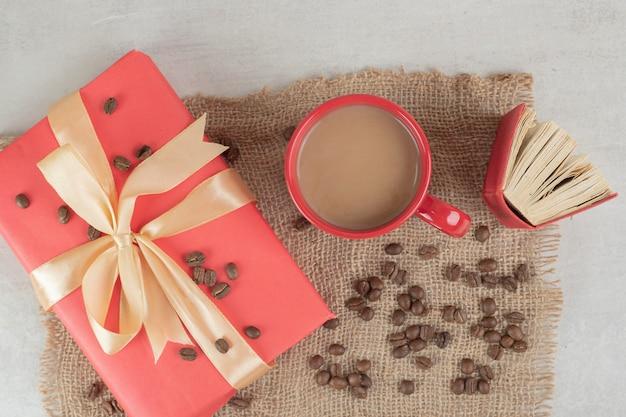 Tasse rouge, livre et grains de café avec boîte-cadeau