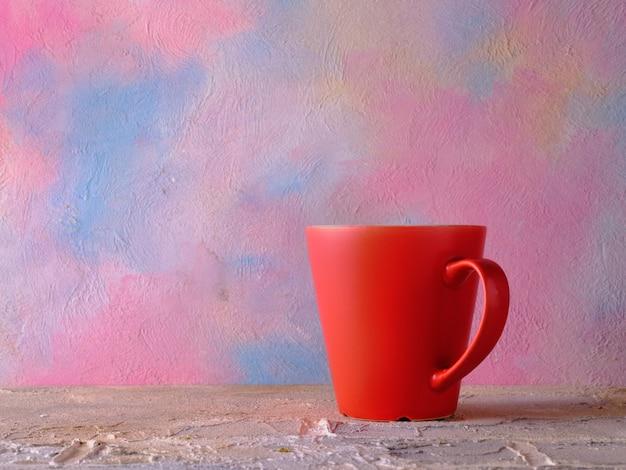 Tasse rouge sur la table contre le mur