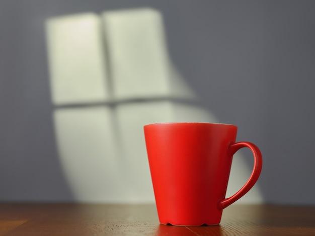 Tasse rouge sur la table et lumière de la fenêtre