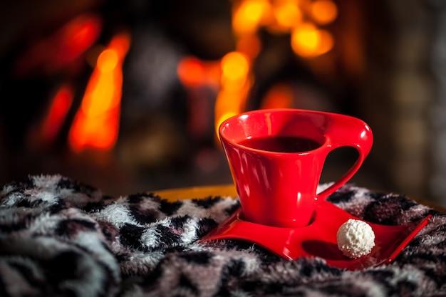 Tasse rouge de thé ou de café et de chocolat près d'une cheminée sur une table en bois.
