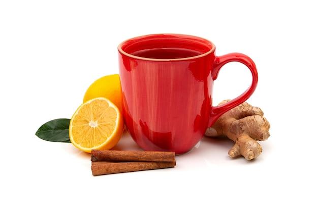 Tasse rouge de thé noir ou vert chaud avec du citron et du gingembre sur fond blanc. ingrédients contre la grippe et les virus. médecine naturelle.