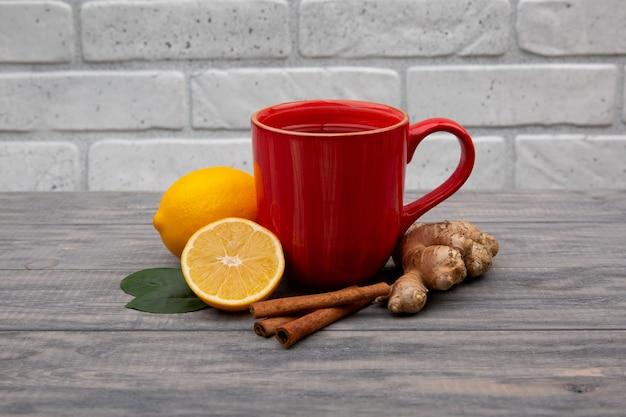 Tasse rouge de thé noir ou vert chaud avec du citron et du gingembre sur un fond en bois. ingrédients contre la grippe et les virus. médecine naturelle.