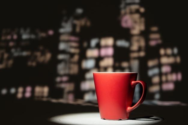 Tasse rouge sur la ville de nuit