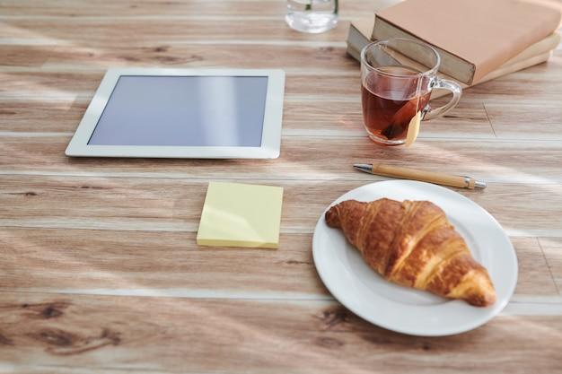 Tasse avec sachet de thé et croissant sur assiette pour le petit-déjeuner à côté de la tablette et pile de livres sur la table de la personne