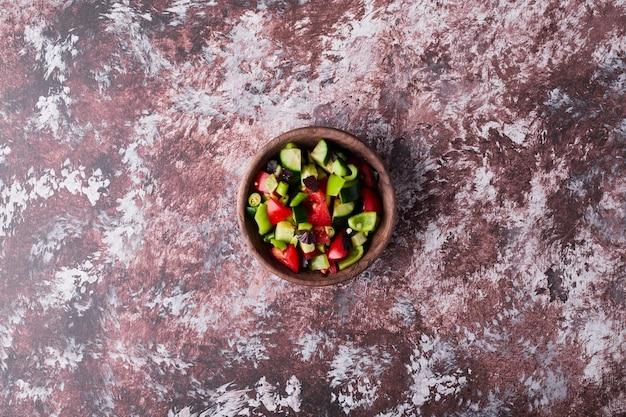 Une tasse de salade de légumes hachés sur le marbre, vue du dessus.