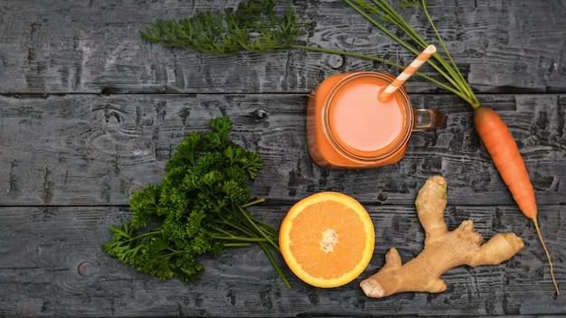 Tasse avec smoothie aux carottes, racine de gingembre et orange sur table sombre rustique en bois.