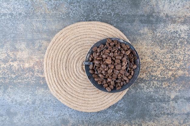 Une tasse sombre pleine de grains de café sur fond de marbre. photo de haute qualité