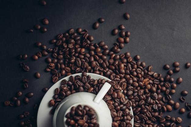Tasse et soucoupe blanche et gros grains de café sur une macro photographie sombre.