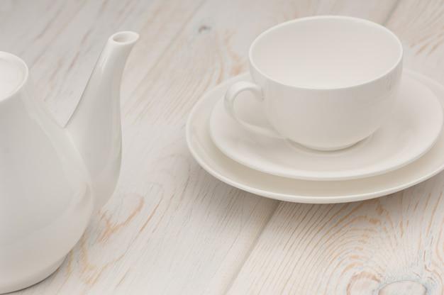 Une tasse et une soucoupe blanches et une bouilloire sur une vieille planche en bois