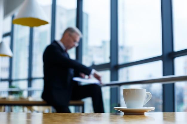 Une tasse et une soucoupe blanches avec du café aromatique chaud se dressent sur une table en bois dans le contexte d'un homme d'affaires assis
