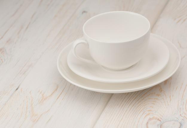 Une tasse et une soucoupe blanches sur une vieille planche de bois