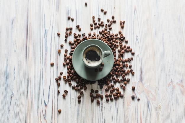 Tasse et soucoupe avec des grains de café autour