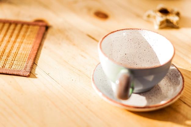 Une tasse et une soucoupe vides se tiennent sur une table en bois. a proximité se trouve une serviette en osier. photo horizontale