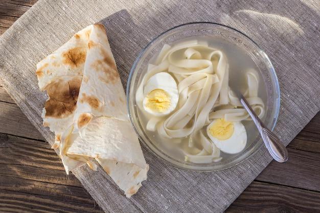 Tasse de soupe au poulet avec nouilles et œufs et pain pita