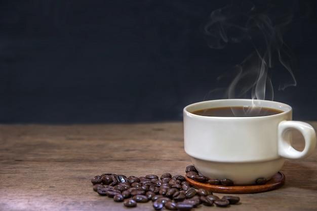Tasse de tasses à café expresso chaud et grains de café torréfiés placés sur le plancher en bois
