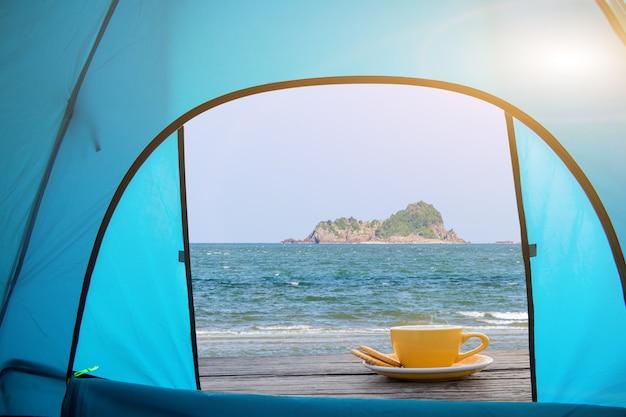 Tasse de tasses à café expresso chaud placé sur un plancher en bois sur la mer vue intérieure tente avec soleil, matin café
