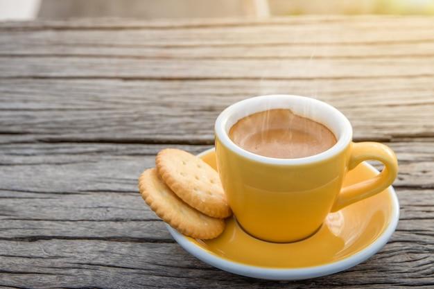 Tasse de tasses à café expresso chaudes placées avec des cookies sur un plancher en bois avec du brouillard du matin et des montagnes avec la lumière du soleil