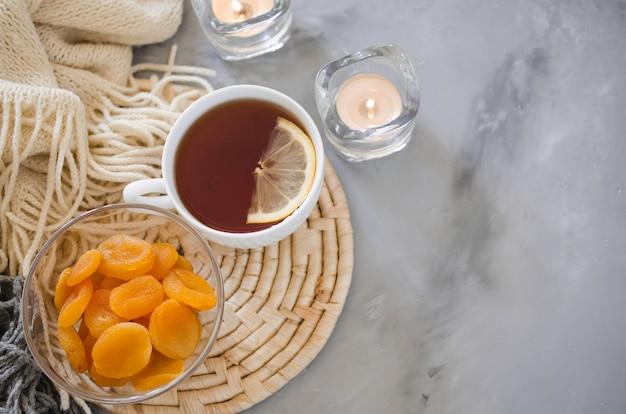 Tasse de thé et d'abricots secs sur une table, bougies et couverture tricotée.