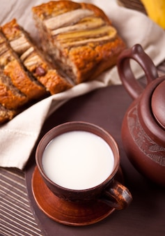 Tasse à thé en argile, théière et pain aux bananes sur une vieille table en bois
