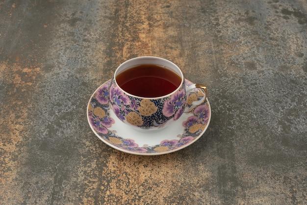 Une tasse de thé aromatique chaud sur un mur de marbre.