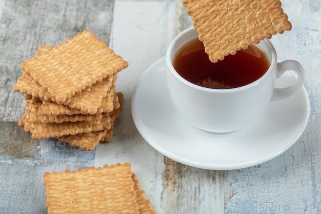 Une tasse de thé aromatique avec des craquelins sur une table en bois.