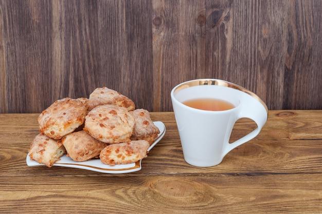 Une tasse de thé et une assiette avec des biscuits maison sur le fond d'une table en bois.