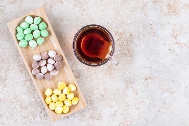 Une tasse de thé et un assortiment de bonbons regroupés dans un petit plateau en bois