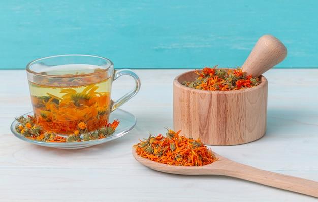 Une tasse de thé au calendula sur une table en bois, un mortier avec des fleurs de calendula