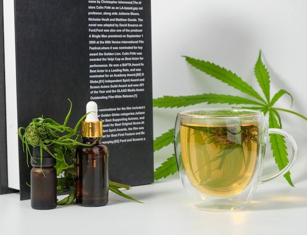 Tasse de thé au cannabis avec des feuilles vertes fraîches de marijuana et des fleurs dans une tasse en verre, une bouteille d'huile de cbd brune et un livre sur une surface blanche.