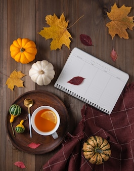 Une tasse de thé au citron, un agenda hebdomadaire et des citrouilles décoratives sur une table en bois marron.
