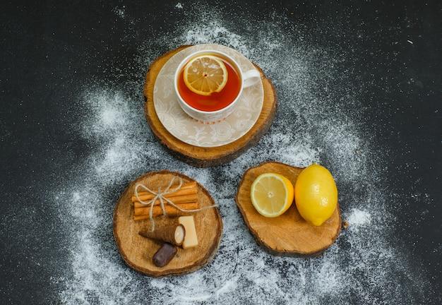 Une tasse de thé au citron, à la cannelle sèche sur des tranches de bois et une vue de dessus sombre.