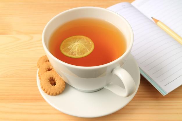 Tasse de thé au citron chaud avec des biscuits et des notes tapissées sur une table en bois