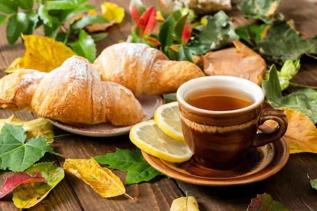 Tasse de thé au citron, croissant, feuilles d'automne