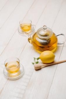 Tasse de thé au citron avec du miel sur fond de bois blanc.