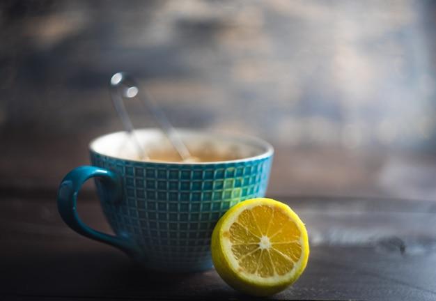 Tasse de thé au citron et épices sur un fond en bois foncé avec espace de copie