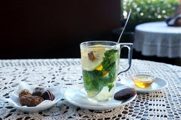 Tasse de thé au citron, menthe, gingembre et dessert
