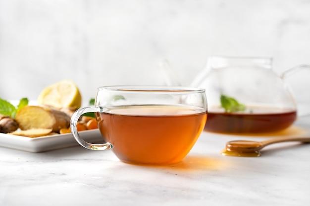 Tasse de thé au citron, miel, curcuma et gingembre sur une surface blanche. aliments d'hiver stimulant le système immunitaire