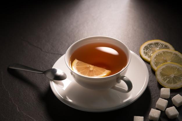 Tasse de thé au citron sur le mur de granit noir