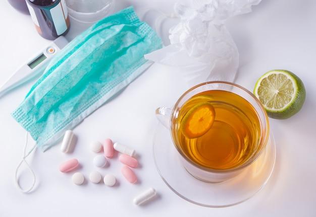 Tasse de thé au citron, thermomètre, médicaments et pilules. concept de maladie. vue de dessus.
