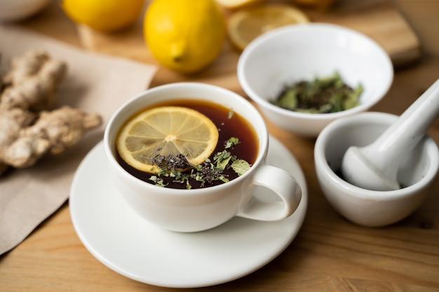 Tasse de thé au gingembre au citron sur fond en bois.