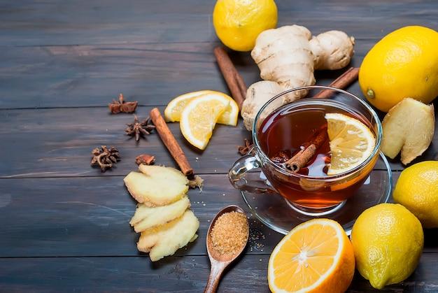 Tasse de thé au gingembre avec citron et miel sur bois brun foncé