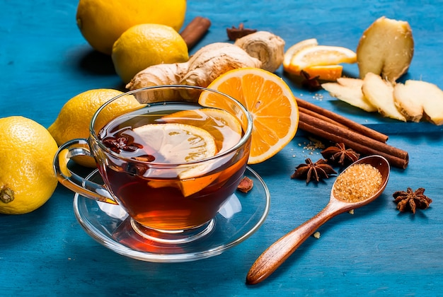 Tasse de thé au gingembre avec citron et miel sur fond bleu foncé,