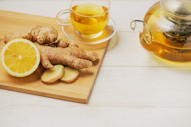 Tasse de thé au gingembre avec citron et miel sur fond de bois blanc.