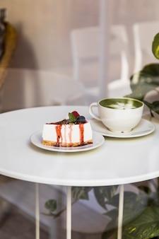 Tasse de thé au lait matcha vert et gâteau au fromage avec sauce aux baies et menthe verte sur tableau blanc