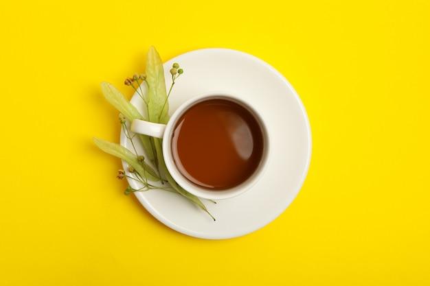 Tasse de thé au tilleul sur jaune, vue du dessus